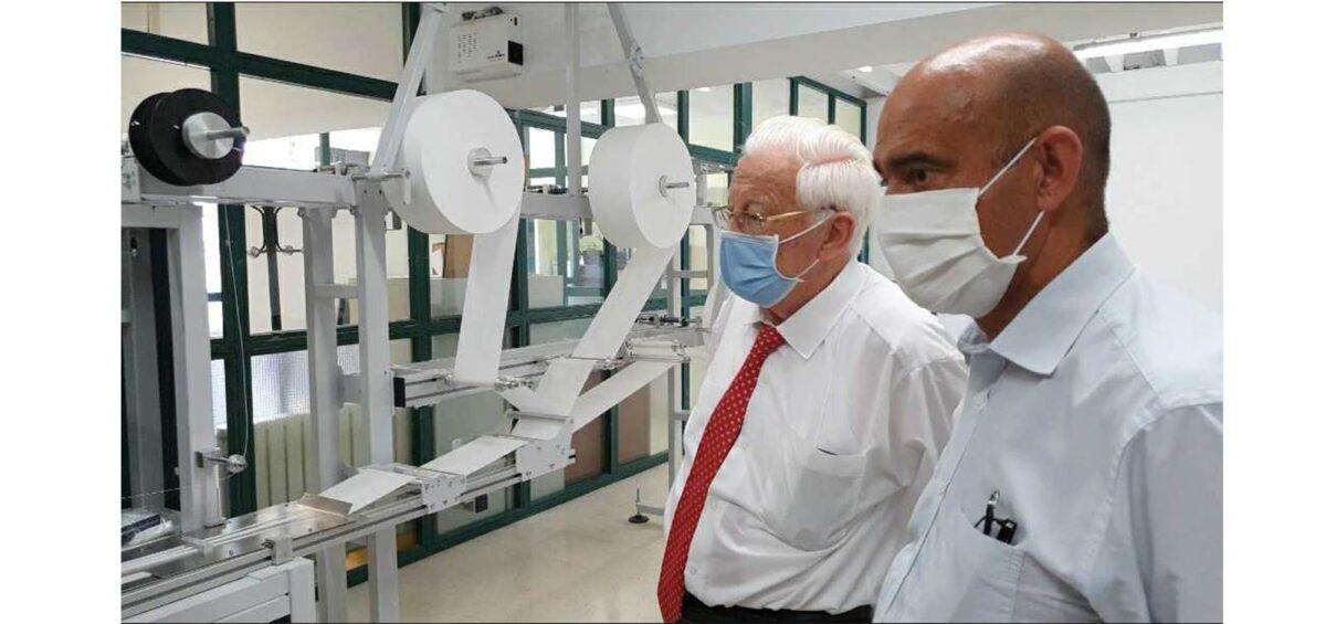Padre Angel y Tomás Castillo ante la maquina de confeccionar mascarillas